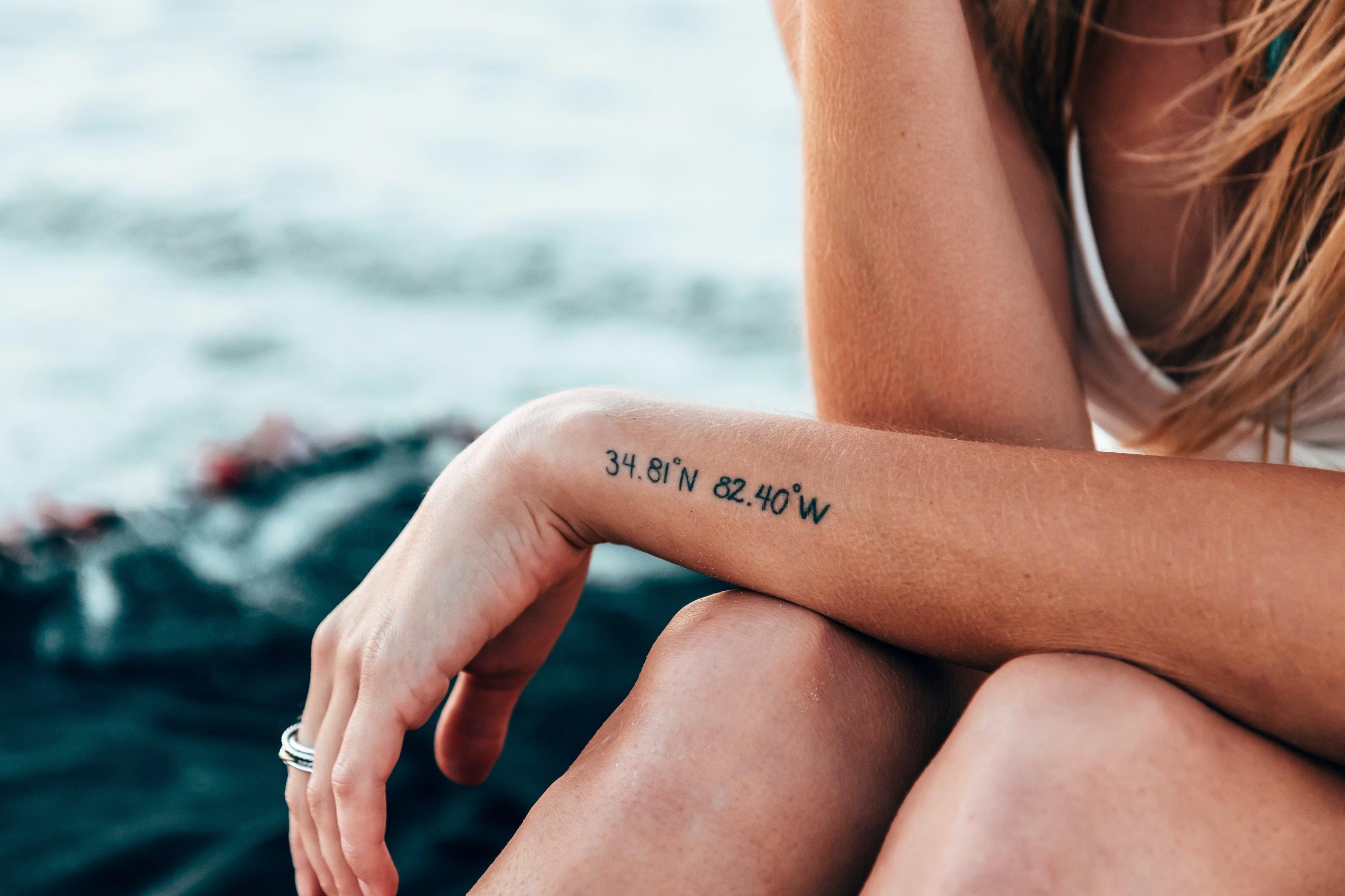 腕にレタリングタトゥーが入った女性
